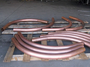 4 1/8 Inch Round 16ga Copper Tubing formed to a 37 In inside radius. This item will be used as down spouts.